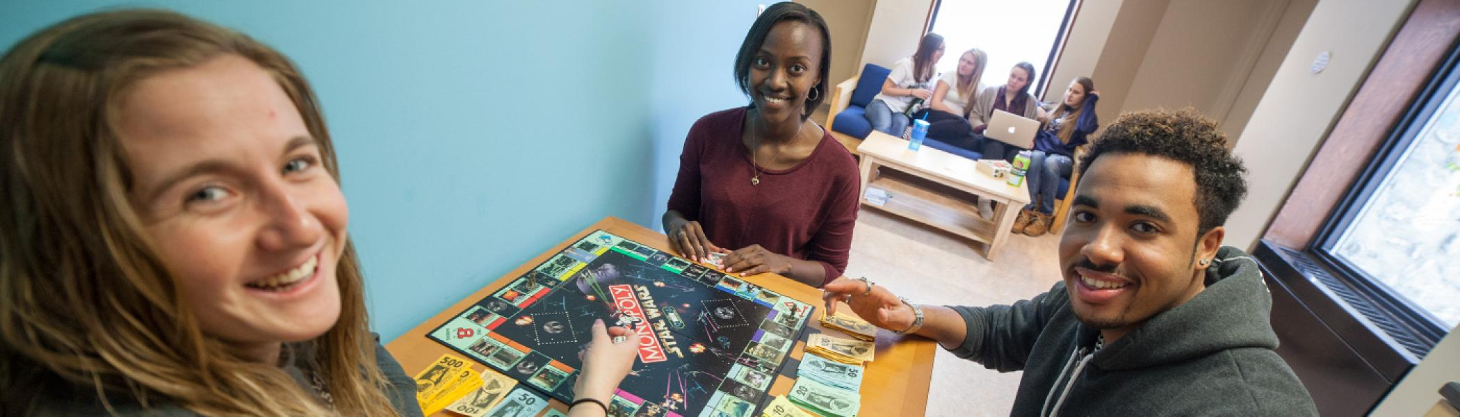 3 Students sitting at a lunch room table playing a board game in Otonabee college