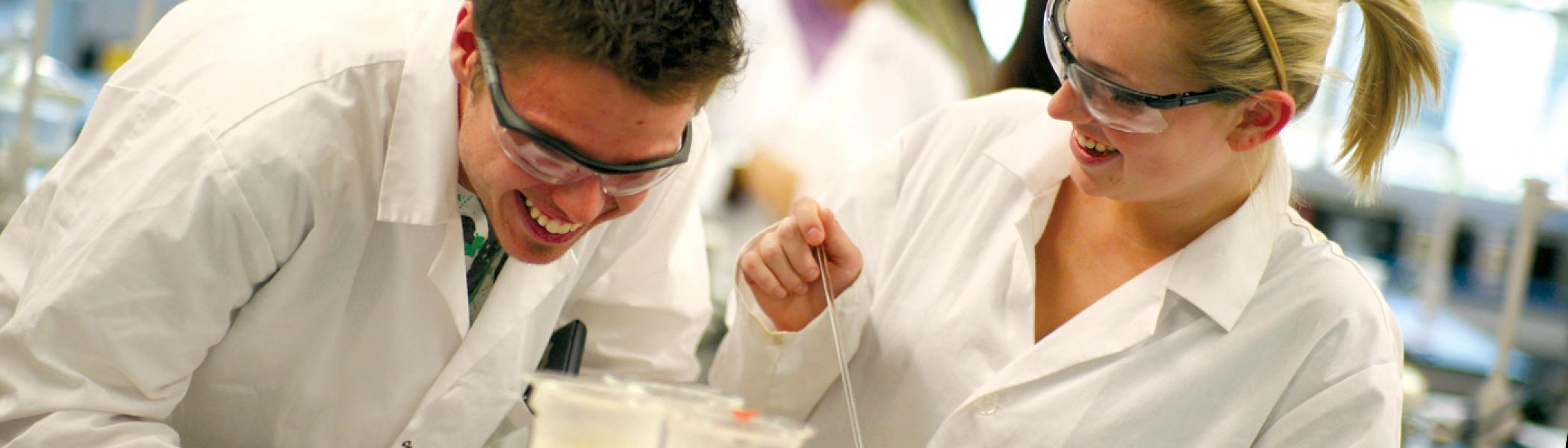 2 Students in lab coats working with test tubes in a schience lab, wearing goggles
