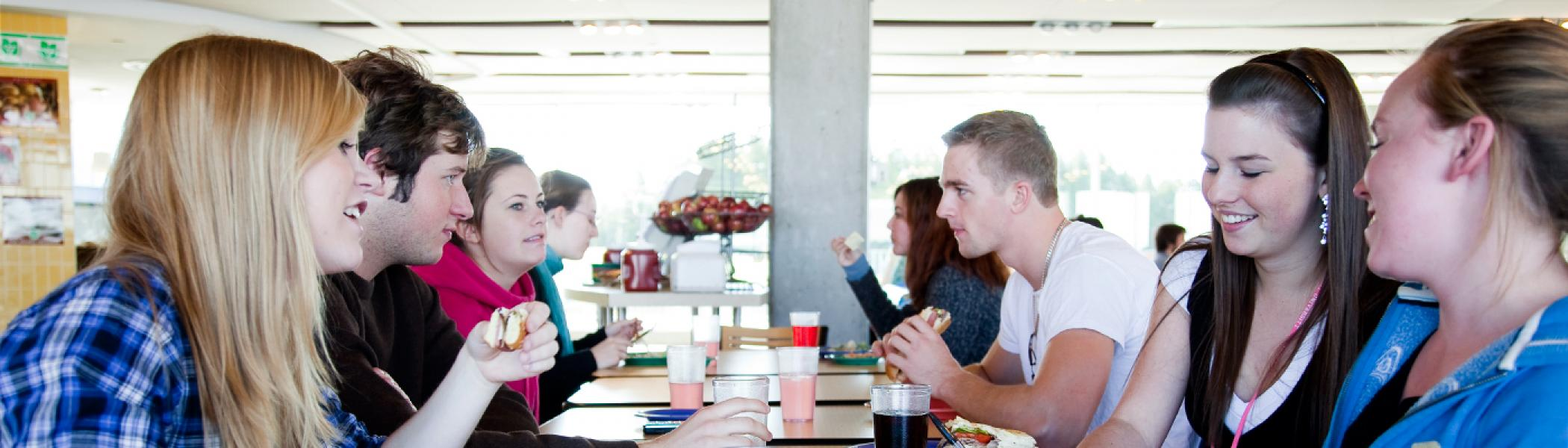 Students gathered in the Gzowski dining hall sitting down eating a one table