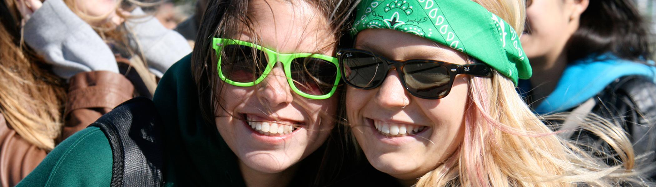 Two students in sunglasses and bandanas smiling at during an outdoor activity in a crowd of people