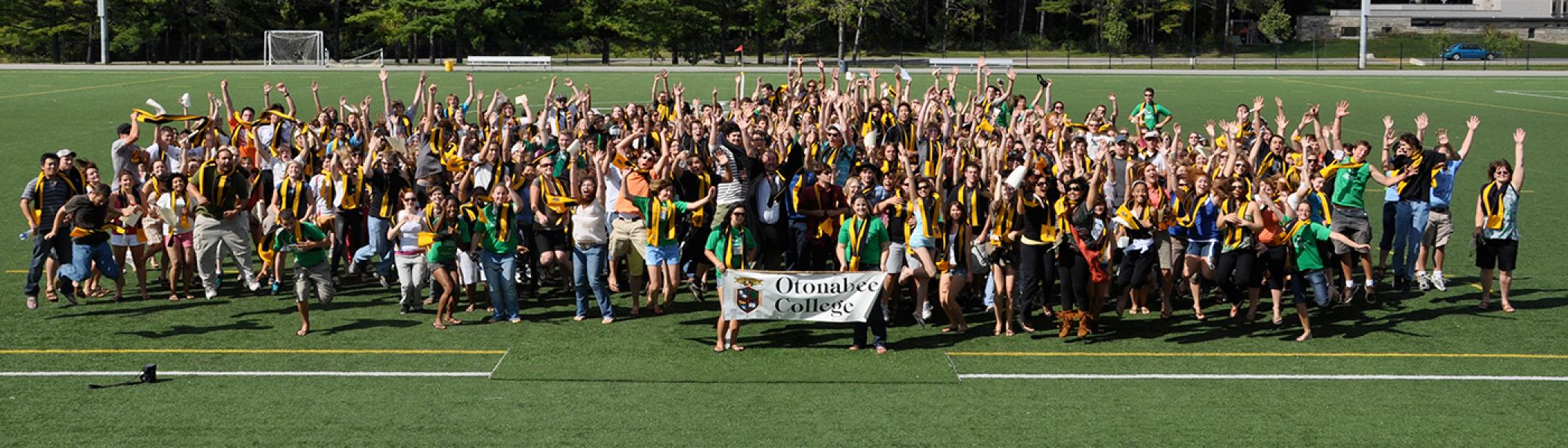 All the occupants fromt he Otonabee residence huddle into a group on the athletics filed for a group photo in the afternoon