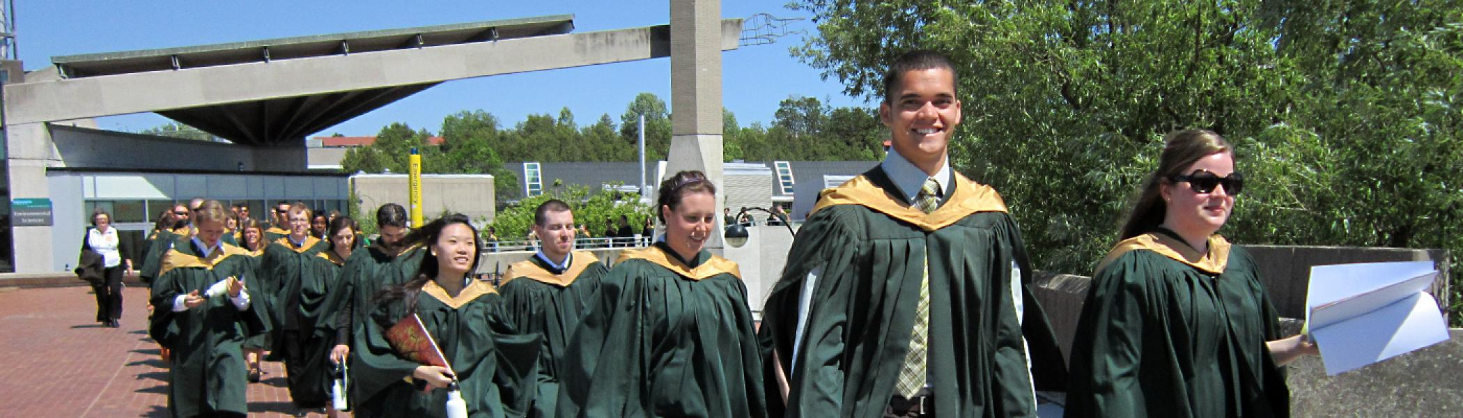 Student walking across the Frayon bridge at convocation in June