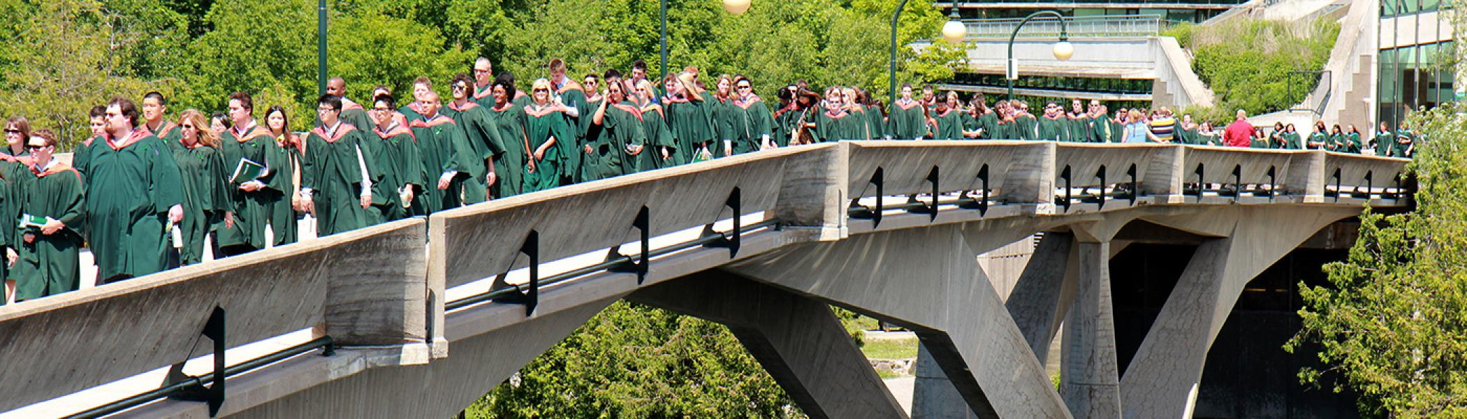 Student crowd of graduating students walking across the Faryon bridge during convocation on a sunny afternoon