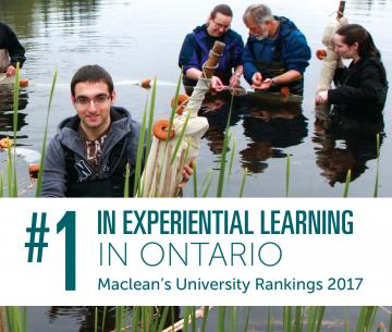 3 students and 1 professor stading in waders in a river looking at algae, while one student smiles at the camera
