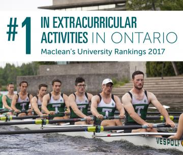 A group of male students sitting in a boat rowing along the Otonabee river on a cloudy summer's morning, wearing their Trent Excalibur outfits