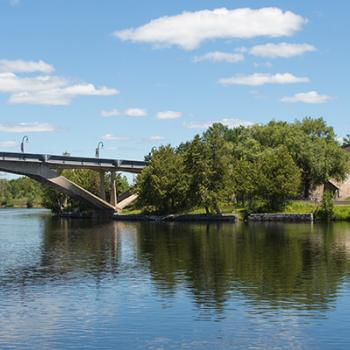 Summertime view looking across the Otonabee river at the Faryon bridge agaisnt a blue sky with white clouds