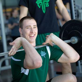 A Trent University student lifting weights in the Athletic Centre.