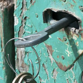 Old skeleton key in an old wooden door with chipped and peeling teal paint