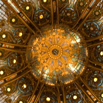 Looking up and intricate stained glass and gold ceiling with an ornate light in the centre.