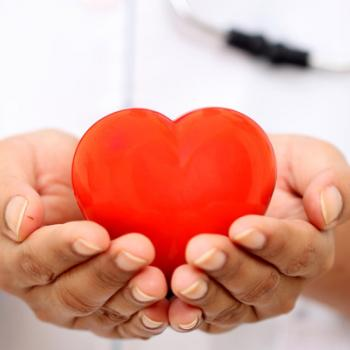 Medical professional holding a heart shape in their open hands.