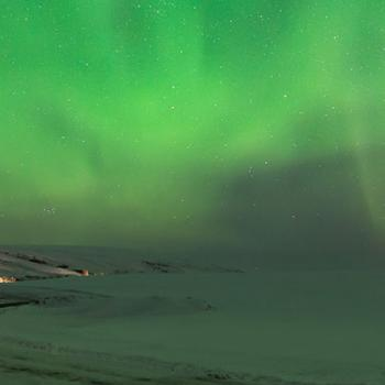 Landscape of a frozen lake and the green northen lights at night