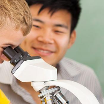 3 Young children, one looking into a microscope as the teacher observes from the background