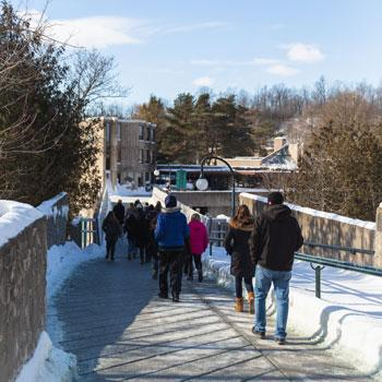 Visitors walking towards Lady Eaton College in winter at Trent University.