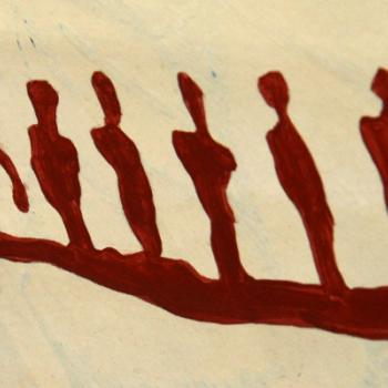 An indigenous paiting of people in a canoe in red paint on wood