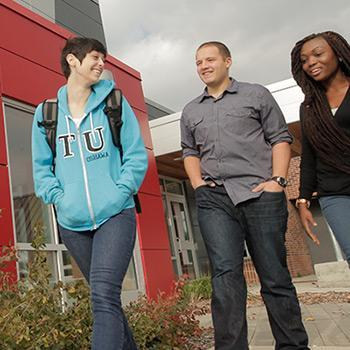 Three students walking past the entrance to Trent University Durham campus