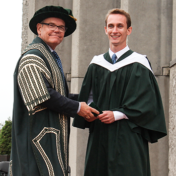 Student receiving an award at convocation on the podium outside of Bata Library in the early afternoon