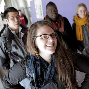 Students standing talking in the main hallway of Otonabee College in front of large window