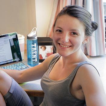 Student sitting at her desk in her Lady Eaton College residence room. Other students lounge on her bed in the background.