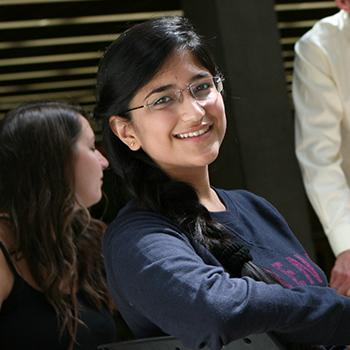 Student with glasses smiling