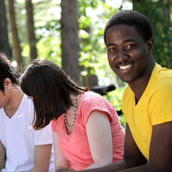 Group of students in woods smiling at camera