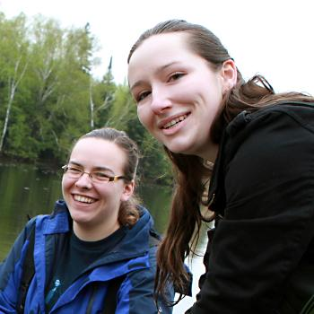 Students standing in a river on a cloudy day gathering river samples