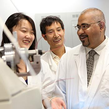 3 Students and Dr. Suresh Narine standing around machinery in the Chemistry lab in their lab coats talking