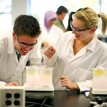 2 Students standing side by side in a chemistry lab in their lab coats with windows in the background