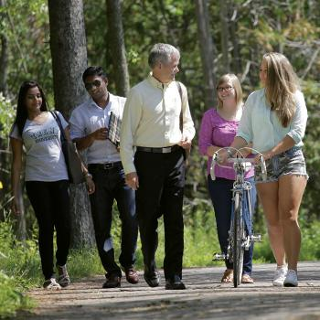 President Leo Groarke walking with students on Peterborough campus