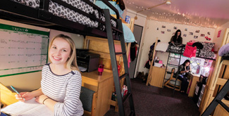 A young female student studying in her dormitory room on campus at Trent University.