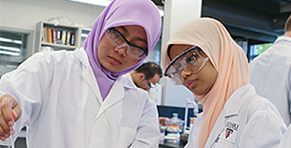 Two biomedical science students in a laboratory.