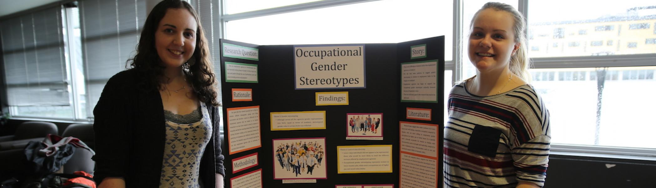 """Two girls standing in front of a poster with the title """"Occupational Gender Stereotypes"""""""