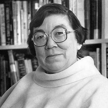 A black and white photo of Margaret Laurence, sitting in front of some bookshelves looking at the camera