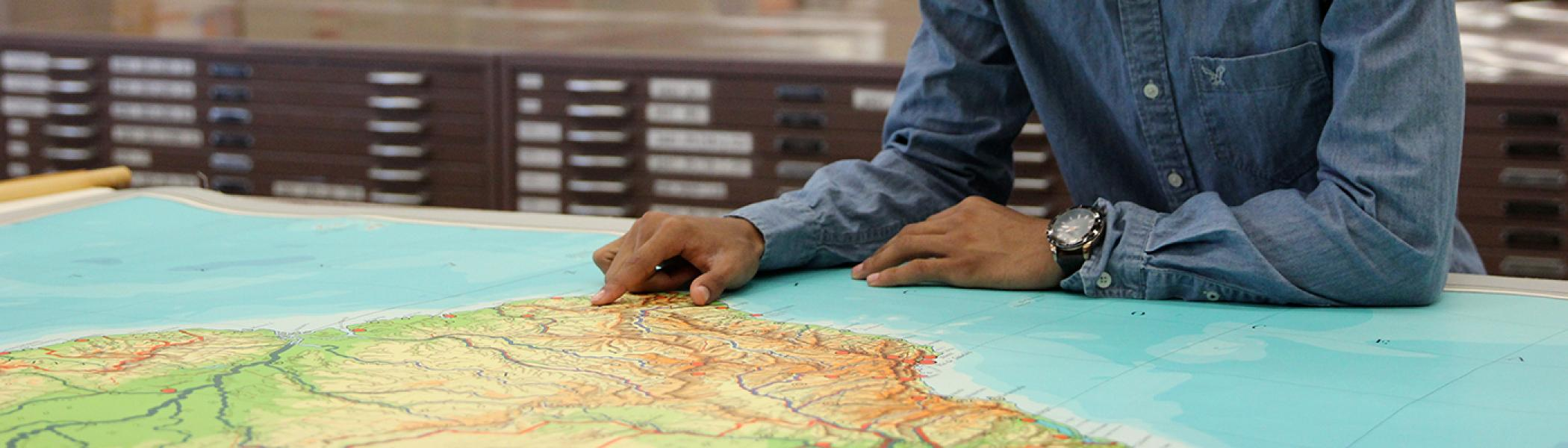 Hand pointing to map