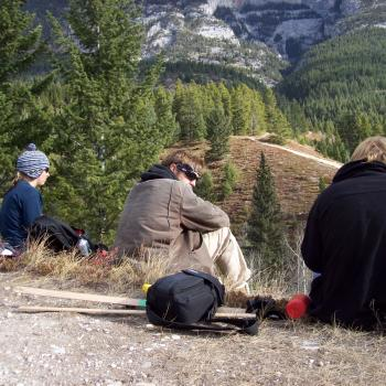 3 students sitting on mountain top in Alberta Canada on fieldwork mission