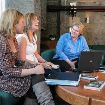 4 women sitting at a round table talking and smiling, in front of a laptop and books