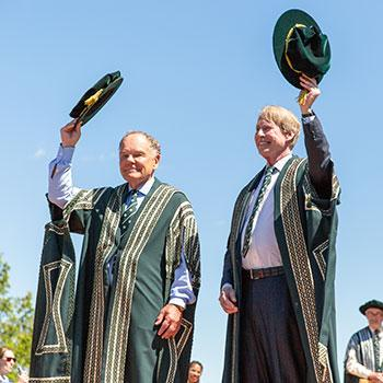 Chancellor Stephen Stohn and Chancellor Don Tapscott lift their caps to the Convocation crowd