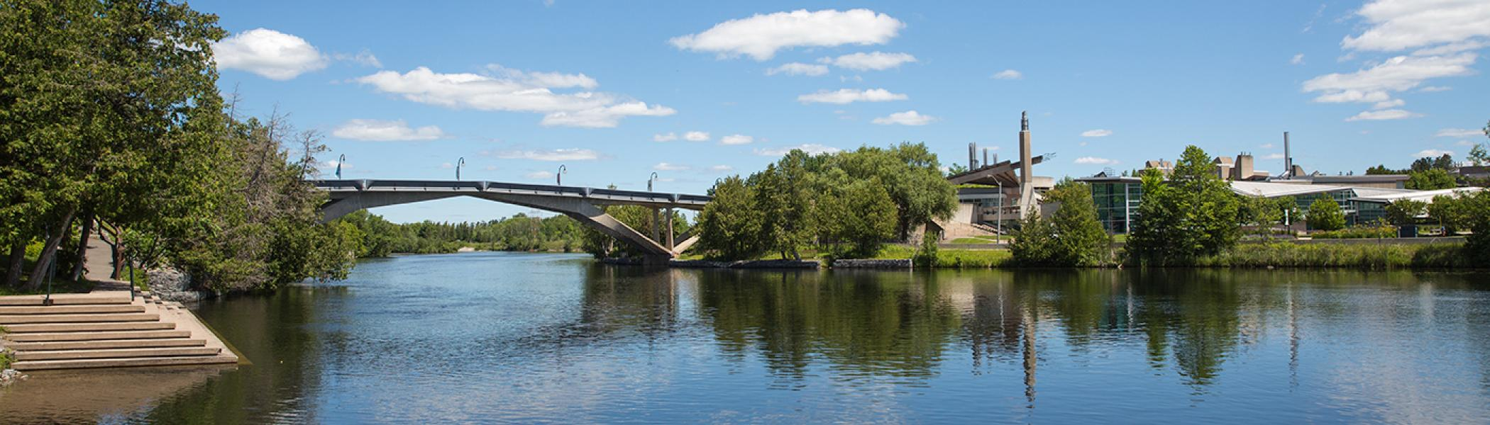 Beauty shot of Symons campus with bridge and Otonabee River