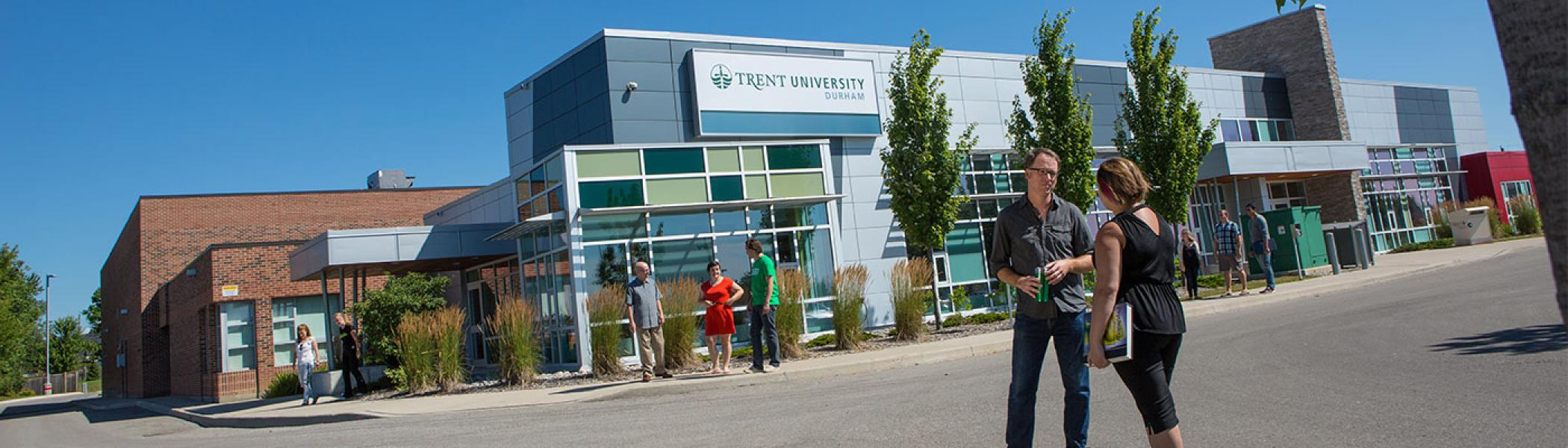 Two people standing in front of Trent University Durham campus building on a sunny day.