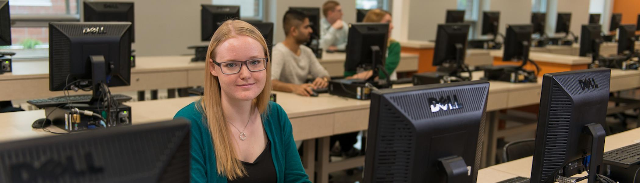A girl working on a computer smiling