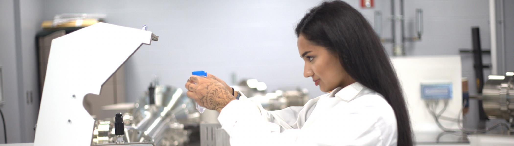 A girl looking at a tube in a lab