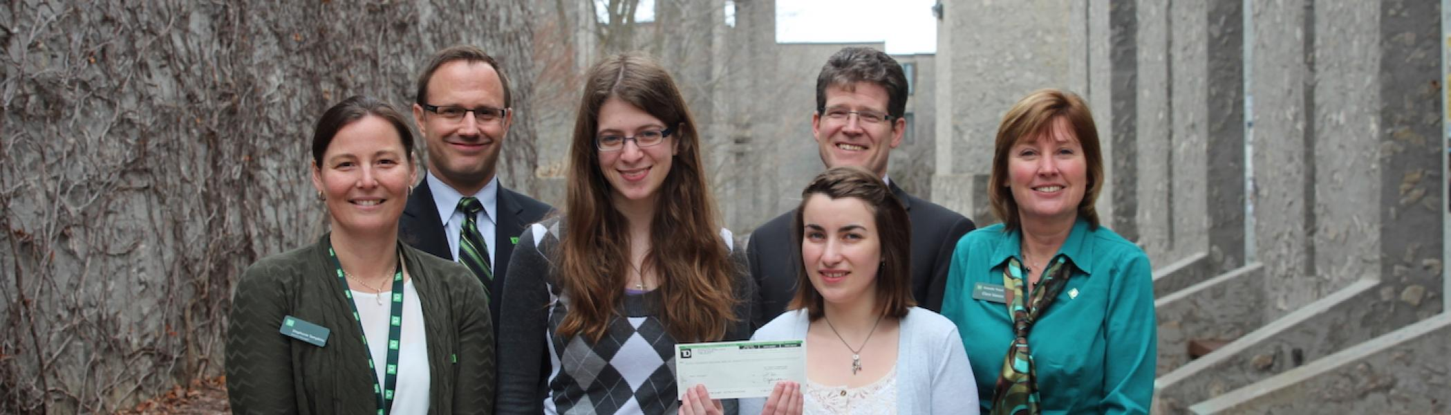 A group of faculty standing with two students holding up a cheque