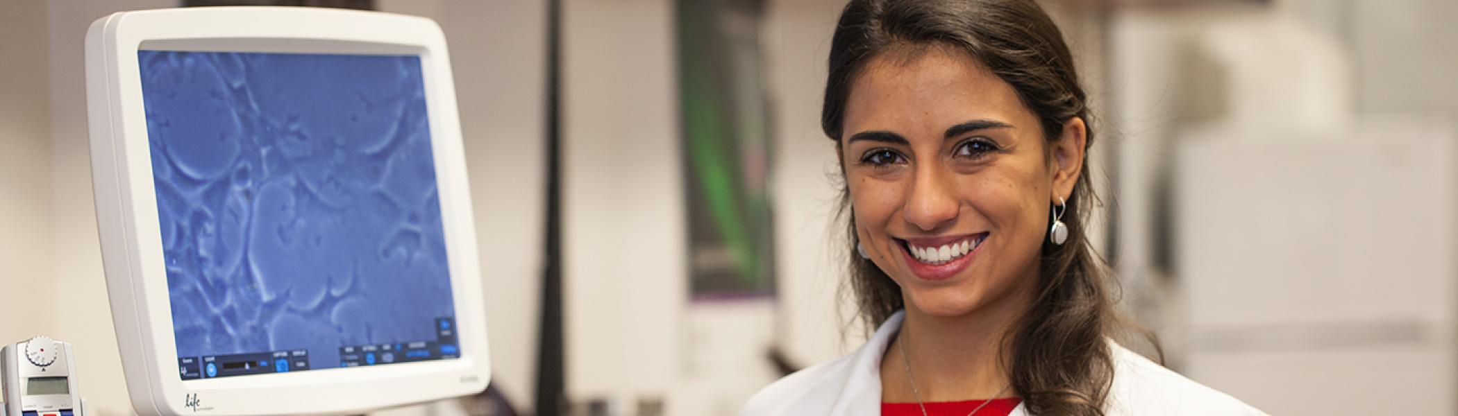 Andressa Lacerda smiling at the camera in a research lab, wearing a whiet lab coat, smiling at the camera