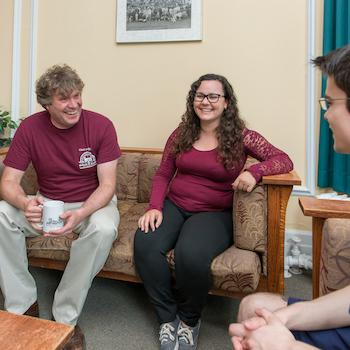 A professor laughing with 2 students sitting on a couch