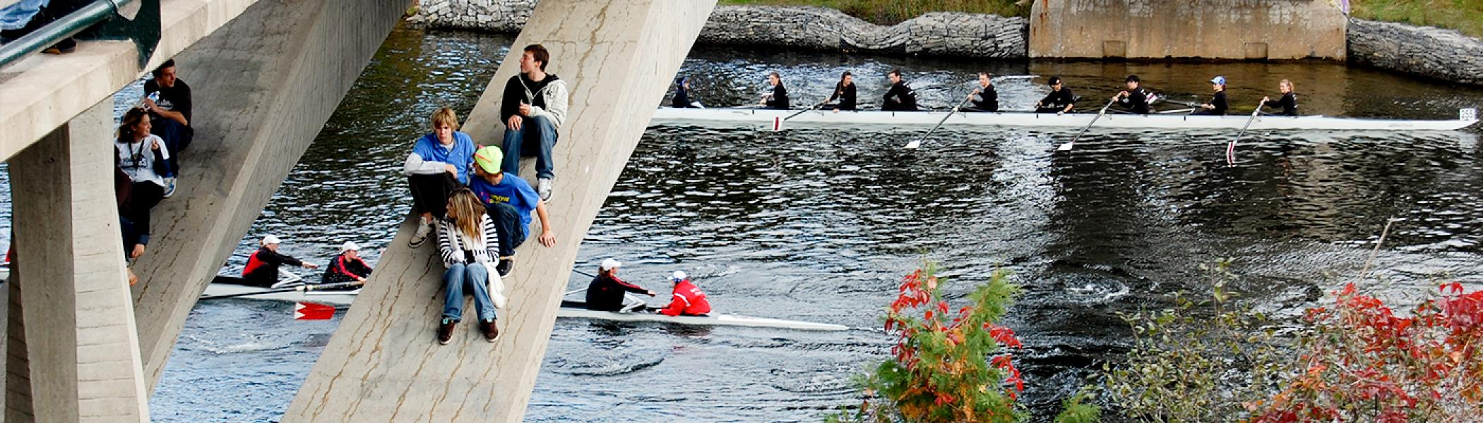 Rowers racing underneath a bridge while students attempt to watch from the bridge supports in a dangerous manner