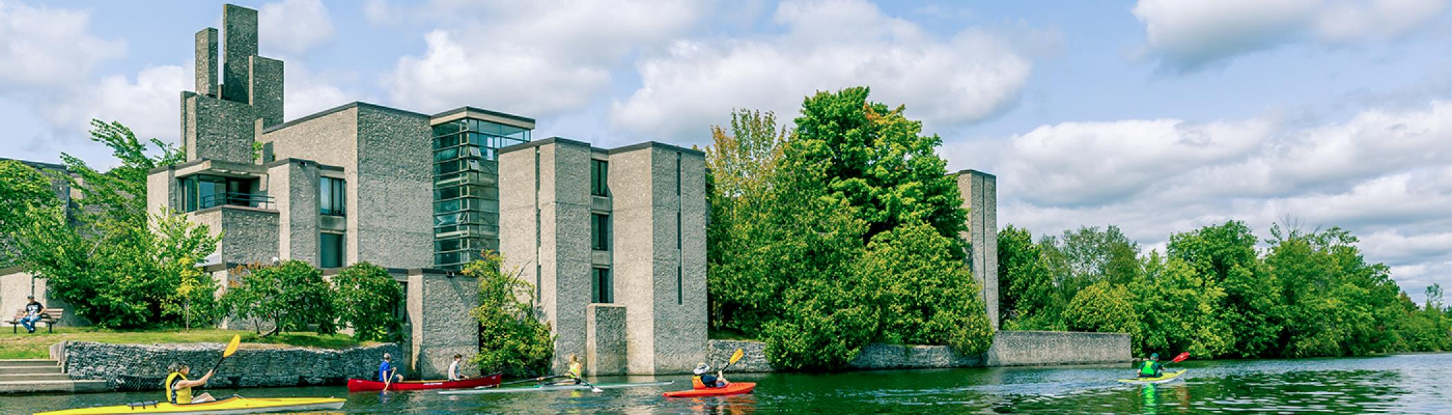 Four people kayaking downstream in front of Champlain college on a sunny day.