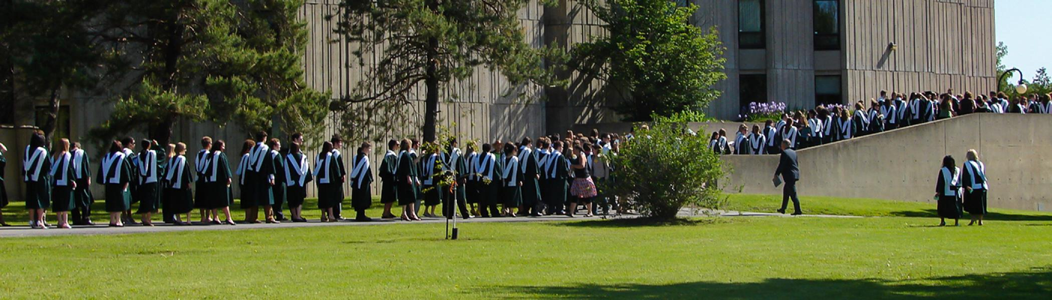 A long line of history graduates waling past Lady Eaton College in their convocation gowns