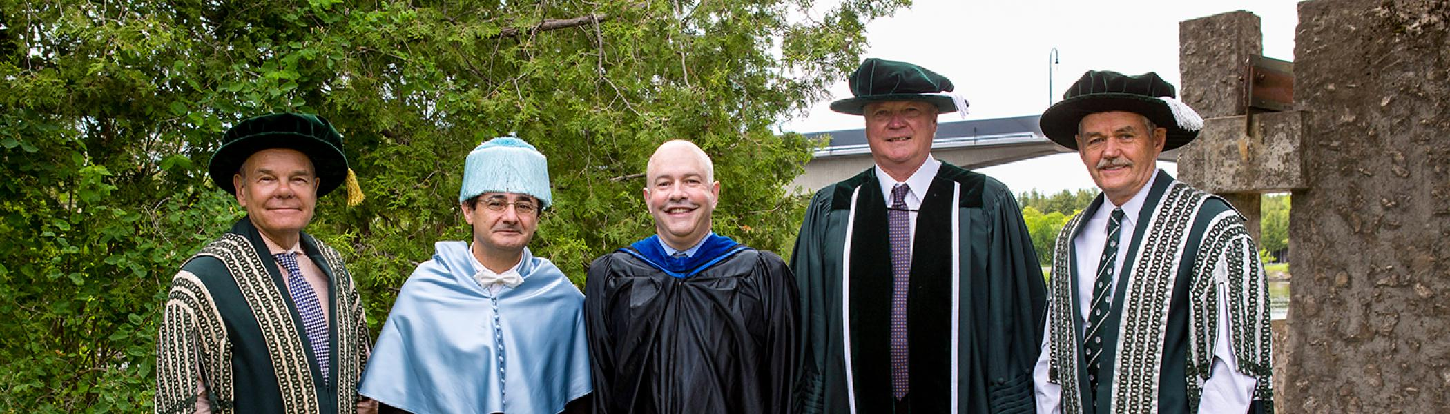 Convocation award winners posing with Dr. Don Tapscott and Leo Groarke in front of the Faryon bridge