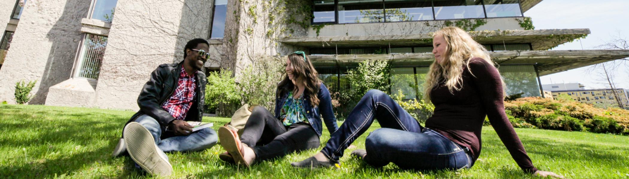 3 History students sitting on the grass in front of the Bata Library chatting