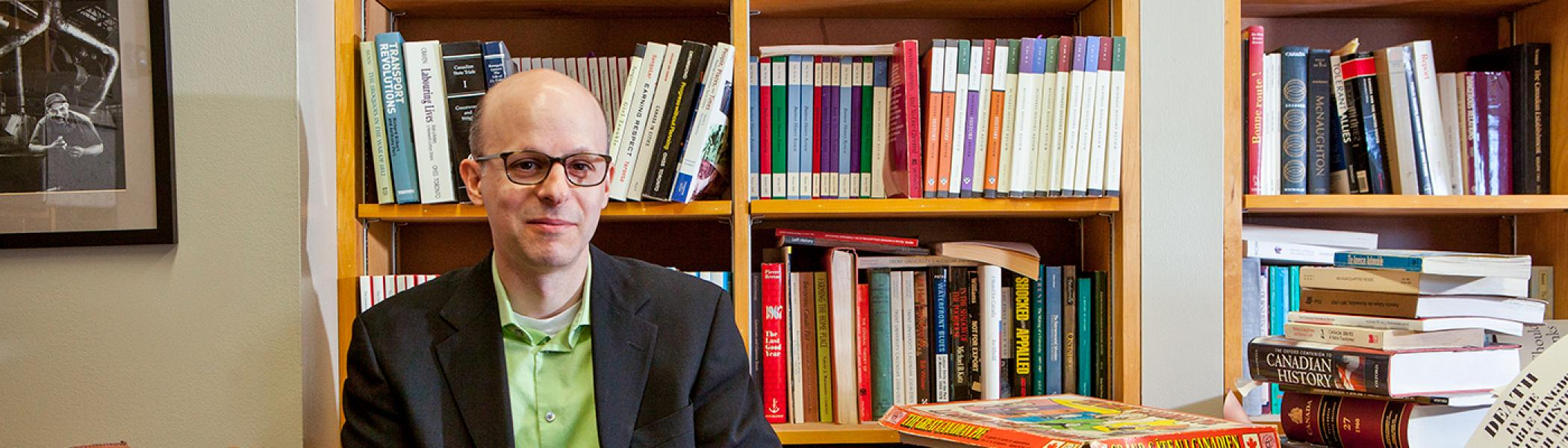 Professor Dimitry Anastakis smiling at the camera, seated in his office in front of a bookcase