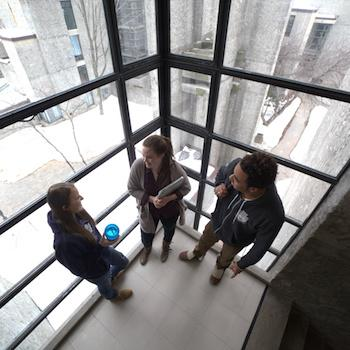 Three students standing in front of a big window with Champlain College in the backgrond